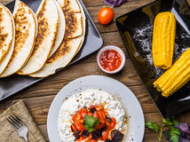Quesadilla, salad with cottage cheese and tomatoes, two corn on wood table. Top wiev. Fresh dinner Stock Photography