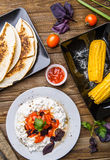Quesadilla, salad with cottage cheese and tomatoes, two corn on wood table. Top wiev. Fresh dinner Stock Photos