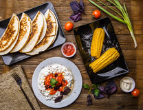 Quesadilla, salad with cottage cheese and tomatoes, two corn on wood table. Top wiev. Fresh dinner Stock Images