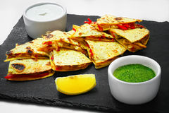 Quesadilla sliced with vegetables and sauces on the table. horiz stock images