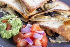 Quesadillas with Salsa. Black bean, mushroom and cheese quesadillas with salsa and guacamole royalty free stock photography