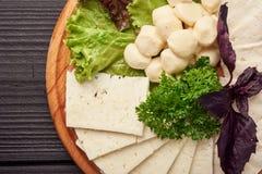 Queso blanco de la cabra con las aceitunas y la salsa dulce en la placa de madera del restaurante fotos de archivo libres de regalías
