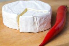Queso blanco del brie en el tablero de la cocina con el papel rojo del chile del chot fotos de archivo