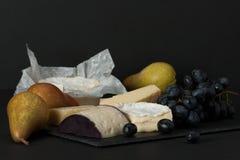 Queso clasificado en piedra de la pizarra Uvas, peras Fotografía de archivo libre de regalías