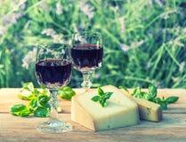 Queso con el vino rojo en la tabla de madera al aire libre Fotografía de archivo libre de regalías