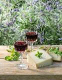 Queso con el vino rojo en la tabla de madera al aire libre Fotos de archivo libres de regalías