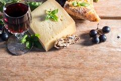 Queso con el vino rojo, las nueces, las hojas de la albahaca y las uvas Foto de archivo libre de regalías