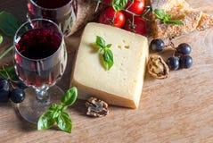 Queso con el vino rojo, las nueces, los tomates, las hojas de la albahaca y las uvas Imagen de archivo libre de regalías