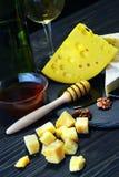 Queso con el vino y la miel en una tabla de madera oscura Imagenes de archivo