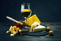 Queso con el vino y la miel en una tabla de madera oscura Foto de archivo