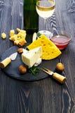Queso con el vino y la miel en una tabla de madera oscura Fotografía de archivo