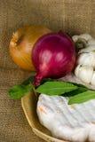Queso con la cebolla, el ajo y hojas frescas de la bahía fotografía de archivo