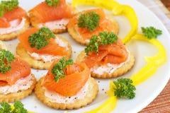 Queso de color salmón y poner crema fumado en las galletas imágenes de archivo libres de regalías