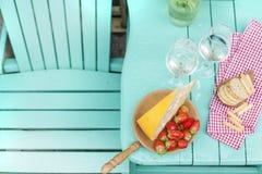 Queso de Holanda y fresas Vino blanco dos vidrios Una tabla con un bocado en un partido Lugar para el texto Copie el sapce imagen de archivo