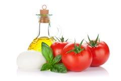 Queso de la mozzarella, aceite de oliva, tomate y albahaca Imagenes de archivo