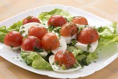Queso de la mozzarella con los tomates en una lechuga verde Fotografía de archivo libre de regalías