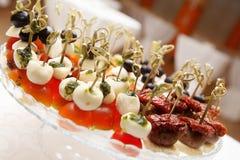 Queso de las aceitunas de los tomates de cereza en el aperitivo de madera del palillo Foto de archivo libre de regalías
