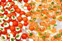 Queso de las aceitunas de los tomates de cereza en el aperitivo del palillo y el salm de madera Imagenes de archivo