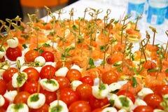 Queso de las aceitunas de los tomates de cereza en el aperitivo del palillo y el salm de madera Imágenes de archivo libres de regalías