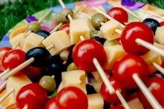 Queso de las aceitunas de los tomates de cereza en el aperitivo de madera del palillo, comida campestre Fotografía de archivo
