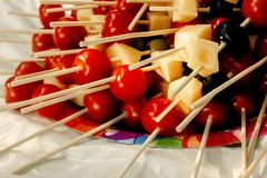 Queso de las aceitunas de los tomates de cereza en el aperitivo de madera del palillo, comida campestre Foto de archivo