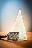 Queso de parmesano con un rallador Imagen de archivo