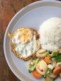 Queso de soja vegetal frito mezclado con arroz y el huevo frito en el plato blanco en fondo de madera Comida vegetariana, comida  Fotos de archivo libres de regalías