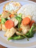 Queso de soja vegetal frito mezclado con arroz y el huevo frito en el plato blanco en fondo de madera Comida vegetariana, comida  Imagenes de archivo