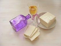 Queso del Adygei en el fondo de madera blanco con el vidrio de vino blanco con la botella Imagen de archivo libre de regalías