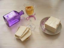 Queso del Adygei en el fondo de madera blanco con el vidrio de vino blanco con la botella violeta Foto de archivo