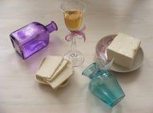 Queso del Adygei en el fondo de madera blanco con el vidrio de vino blanco con las botellas de la violeta y del trullo Imágenes de archivo libres de regalías
