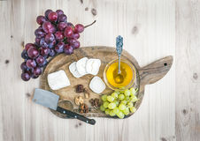 Queso del brie de la cabra con las uvas y la miel frescas en un de madera rústico Fotografía de archivo