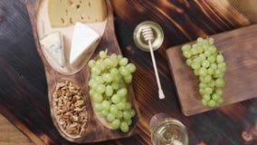Queso del brie, del Gouda y del Roquefort en una composición hermosa con el vino blanco metrajes