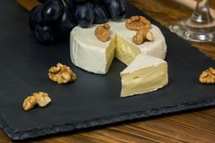 Queso del camembert en una bandeja oscura al lado de nueces y de la miel azules dulces de las uvas fotos de archivo libres de regalías