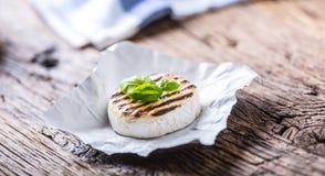 Queso del camembert Queso asado a la parrilla del camembert con las hojas del aceite y de la albahaca de oliva imágenes de archivo libres de regalías