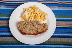Queso del pan con carne y de los macarrones en Placemat rayado Imagen de archivo libre de regalías