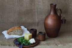 Queso duro y suave con verdes en la placa redonda de la arcilla, el jarro para el vino, la taza y el pan en el pa?o blanco en fon fotos de archivo libres de regalías