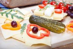 Queso en el pan alemán con la pimienta dulce, uvas, pepino, tomates Fotos de archivo libres de regalías