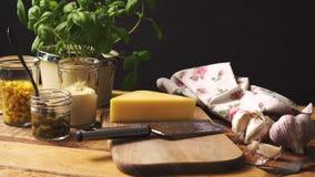 Queso en la tajadera y el rallador con albahaca fresca en la tabla de cocina de madera metrajes