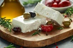 Queso Feta griego del queso con tomillo, romero, aceitunas y paprikas rojos rellenos foto de archivo libre de regalías