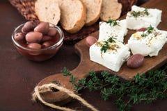 Queso Feta griego del queso con tomillo y aceitunas Foco selectivo, copia Imagen de archivo libre de regalías