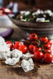 Queso feta hecho en casa con los tomates de cereza y el fondo griego de la ensalada en la tabla de madera imagen de archivo