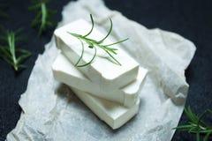 Queso Feta orgánico del queso de cabra con romero en el papel de pergamino imagen de archivo libre de regalías
