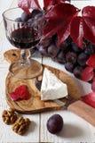 Queso francés Coulommiers, vidrio de vino rojo, de nueces y de uvas Foto de archivo libre de regalías