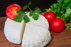 Queso fresco con gusto y el aroma excelentes Queso en tabla de cortar de madera con los tomates y las hierbas frescas fotografía de archivo libre de regalías