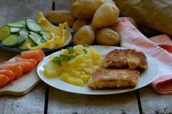 Queso frito con las patatas peladas de cosecha propia en fondo de madera Fotos de archivo libres de regalías
