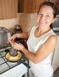 Queso grating de la mujer en la tortilla de huevos fotos de archivo