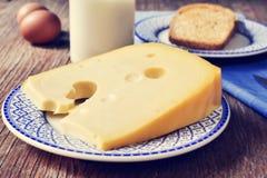 Queso, leche, huevos y pan en una tabla de madera rústica, con un fi Fotos de archivo
