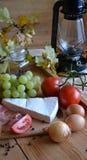 Queso, pan, cebollas, vino, tomates y una lámpara de keroseno Imagenes de archivo
