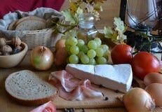 Queso, pan, cebollas, vino, tomates y una lámpara de keroseno Imágenes de archivo libres de regalías